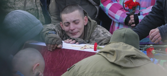 A comrade cries during the funeral ceremony for servicemen Sergey Kochetov and Nikolay Sayuk, Ukrainian volunteers from 'Aydar Battalion' who were killed in a war conflict in eastern Ukraine, at the Independence Square in Kiev, Ukraine. Nov 4. 2016.