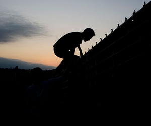 A migrant jumps to cross the U.S. Mexico border fence in Tijuana in 2008.
