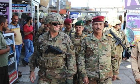 In this October photo, Lt. Gen. Paul Funk, left, commanding general of Combined Joint Task Force-Operation Inherent Resolve, and Iraqi Maj. Gen. Najm Abdullah al-Jibouri, right, walk through a busy market near the University of Mosul.