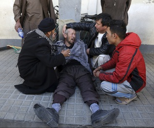 A distraught man is cared for outside a hospital following a suicide attack in Kabul, Afghanistan, Thursday that killed dozens.