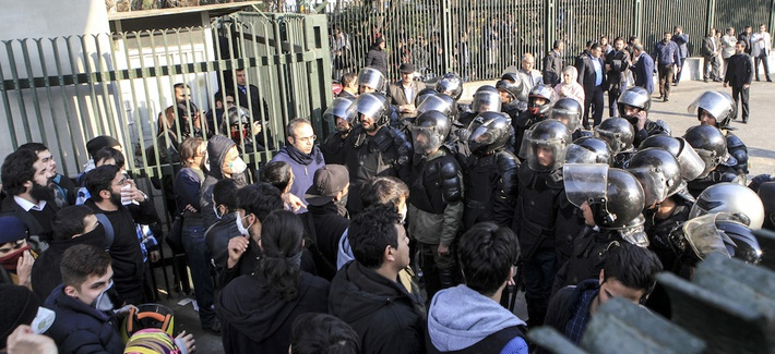 In this photo taken by an individual not employed by the Associated Press and obtained by the AP outside Iran, anti-riot Iranian police prevent university students to join other protesters over Iran weak economy, in Tehran, Iran, Saturday, Dec. 30, 2017.