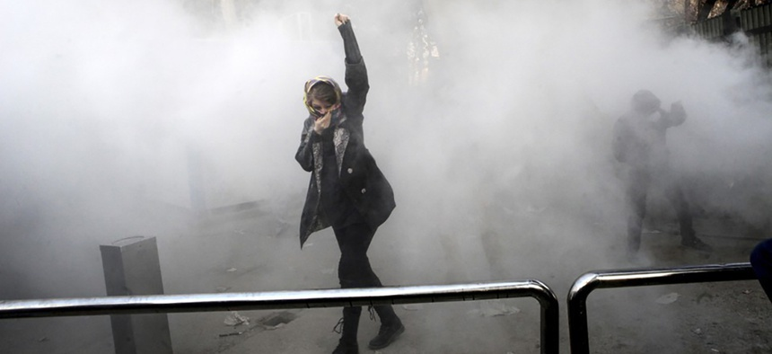 Students attend a protest at Tehran University, where a smoke grenade was thrown by anti-riot Iranian police on December 30, 2017.