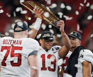Alabama's Tua Tagovailoa holds up the national championship trophy after the team's victory.