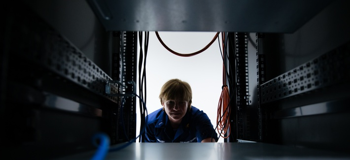 A U.S. Coast Guard officer peers through a space in a server at Coast Guard Base Boston, April 20, 2017.