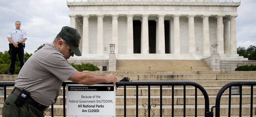 A U.S. Park Police officer watches at left as a National Park Service employee posts a sign on a barricade closing access to the Lincoln Memorial in Washington.