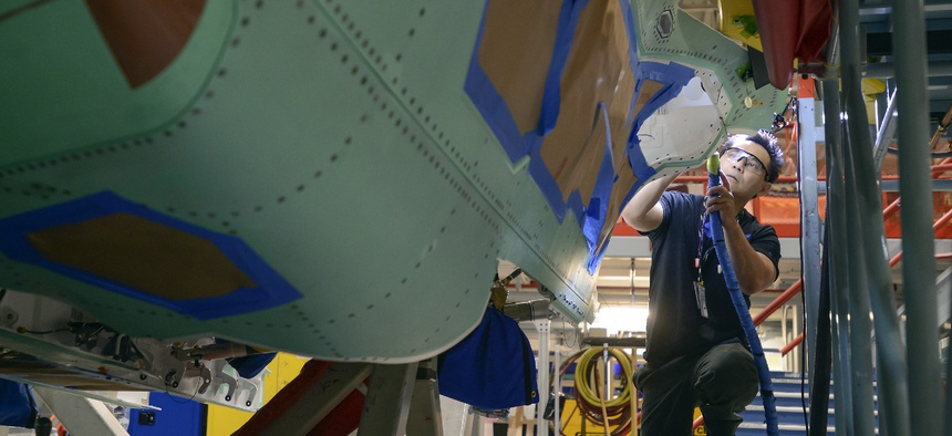 A Northrop Grumman technician puts finishing touches on an F-35 fuselage.