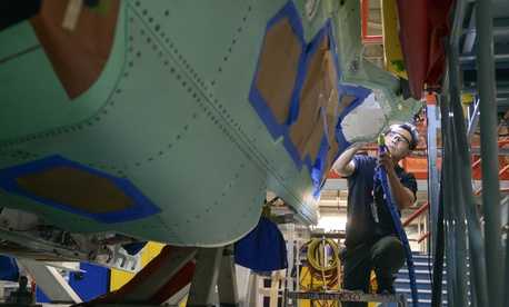 A Northrop Grumman technician puts finishing touches on an F-35 fuselage.