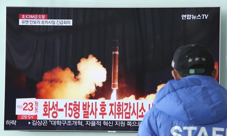 A man watches a TV screen showing what the North Korean government calls the Hwasong-15 intercontinental ballistic missile.