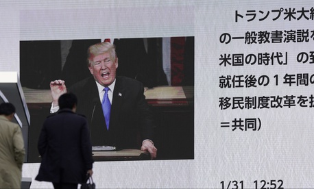 People walk by a huge screen showing a news program reporting U.S. President Donald Trump's State of the Union address, in Tokyo, Wednesday, Jan. 31, 2018.