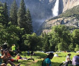 Visitors sit in a meadow at Yosemite National Park, Calif., below Yosemite Falls.