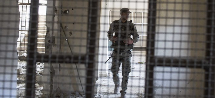 A Syrian Democratic Forces fighter in the liberated soccer stadium-turned-prison where ISIS held locals, Raqqa, Syria, Friday, Oct. 20, 2017. Now, SDF is holding captive 'hundreds' of ISIS foreign fighters.