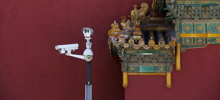 Surveillance cameras stand next to the figurines on a main entrance gate of the Imperial Ancestral Temple, or Taimiao next to the Forbidden City in Beijing, Sept. 17, 2017.