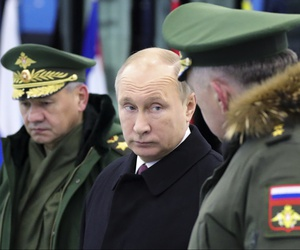 Russian President Vladimir Putin speaks to Russian Strategic Missile Troops Commander, Col. Gen. Sergei Karakayev, right, as Russian Defence Minister Sergei Shoigu looks on outside Moscow, Russia, Dec. 22, 2017.