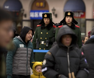 Chinese paramilitary police stand guard outside of the Beijing Railway Station in Beijing, Friday, Feb. 9, 2018.