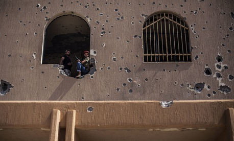 A fighter of the Libyan forces affiliated to the Tripoli government rests in the battle against Islamic State fighters in Sirte, Libya, Sept. 29, 2016.