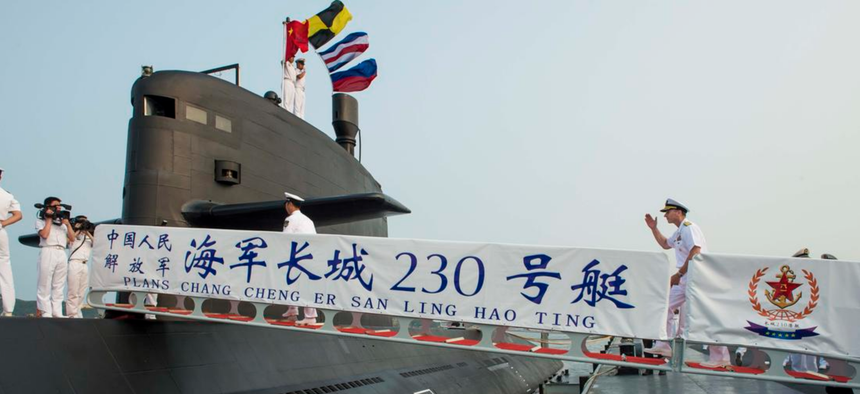 Chief of Naval Operations (CNO) Adm. Jonathan Greenert crosses the brow and boards a People's Liberation Army Navy (PLAN) Type-39B submarine for a pierside tour on Lushun Naval Base in 2014.