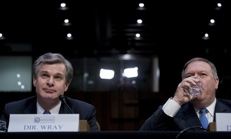FBI Director Christopher Wray, left, and CIA Director Mike Pompeo, right, appear before a Senate Select Committee on Intelligence hearing on worldwide threats, Tuesday, Feb. 13, 2018, in Washington
