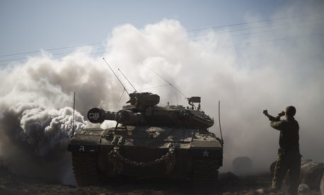 An Israeli soldier directs a tank near the border with Syria in the Israeli-controlled Golan Heights,Nov. 28, 2016.