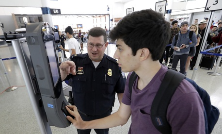 A U.S. Customs and Border Protection officer helps a passenger navigate one of the new facial recognition kiosks at a United Airlines gate at George Bush Intercontinental Airport, in Houston, July 12, 2017.