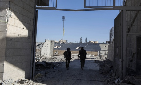 Members of the U.S.-backed Syrian Democratic Forces (SDF) enter the stadium that was the site of Islamic State fighters' last stand in the city of Raqqa, Syria, Oct. 18, 2017.