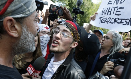 "In this Aug. 19, 2017 file photo, a supporter of President Donald Trump, center, argues with a counterprotester, left, at a ""Free Speech"" rally by conservative activists on Boston Common in Boston."