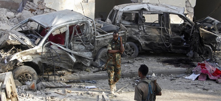 Somali soldiers stand near the wreckage of vehicles in Mogadishu, Somalia, in October, after a car bomb detonated.