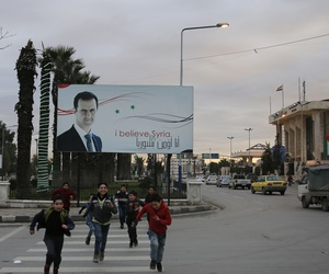 In this Jan. 19, 2018 photo, Syrian children cross a street in front a banner showing Syrian President Bashar Assad, in Aleppo, Syria.