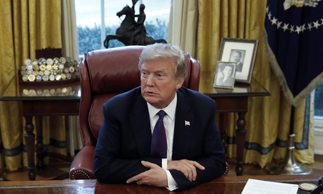 President Donald Trump sits at the Resolute Desk in the Oval Office of the White House in Washington, Jan. 23, 2018.