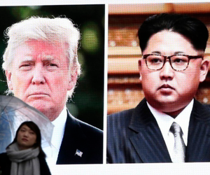 A woman walks by a huge screen showing Donald Trump, left, and Kim Jong Un, in Tokyo, Japan, on March 9, 2018.