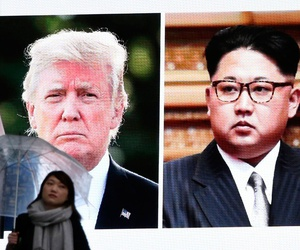 A woman walks by a huge screen showing Donald Trump and Kim Jong Un in Tokyo on March 9.