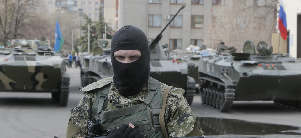 A masked gunman guards combat vehicles with Russian, Donetsk Republic and Ukrainian paratroopers, flags and gunmen on top, parked in downtown of Slovyansk on Wednesday, April 16, 2014.