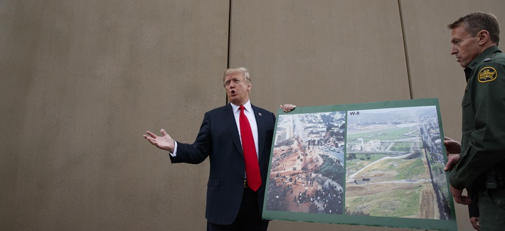 President Donald Trump talks with reporters as he gets a briefing on border wall prototypes, March 13, 2018, in San Diego.