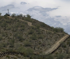 A US National Guard vehicle guards covered under camouflage fabric sits atop a mountain next to the border fence near Sonoyta, Mexico, Thursday, July 29, 2010.