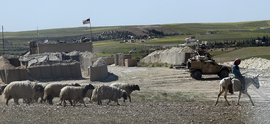 A Syrian shepherd herds his flock, as he passes in front of a newly installed U.S. position near the tense front line between the U.S-backed Syrian Manbij Military Council and the Turkish-backed fighters, in Manbij, north Syria, Wednesday, April 4, 2018.