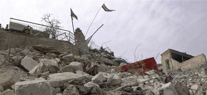 In this frame grab from video, a body lies under the Iraqi flag in the Maydan district of Mosul's Old City, Iraq, Wednesday, March 7, 2018.