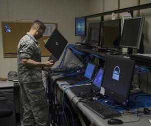 An airman prepares to image a laptop at Yokota Air Base, Japan.