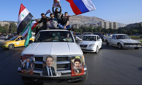 Hundreds of Syrians demonstrated on April 14 in a landmark square in the Syrian capital, waving victory signs and honking their car horns in a show of defiance after U.S.-led airstrikes on their country.