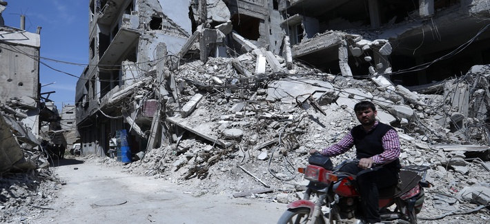 A man rides past destruction in the town of Douma, the site of a suspected chemical weapons attack, near Damascus, Syria, Monday, April 16, 2018.