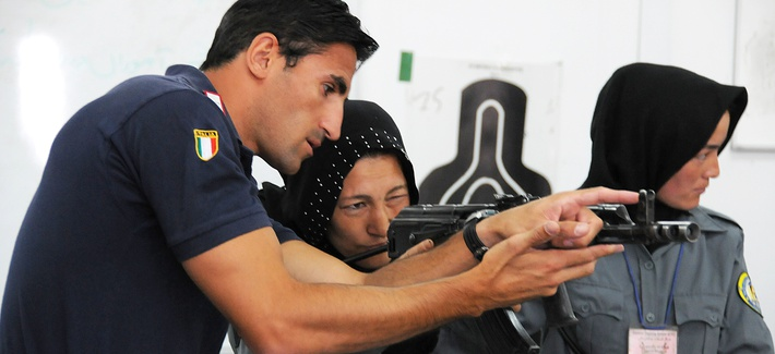 An Italian Carabinieri shows a female Afghan National Police recruit how to aim an AMD-65, a Hungarian version of the AK-47, during an eight-week basic police training course at the Central Training Center in Kabul.