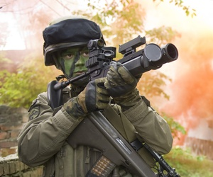 An Panzergrenadier of the Austrian armed forces protects the area with a grenade rifle, while an Ulan armored personnel carrier drives up on the outskirts of a village .