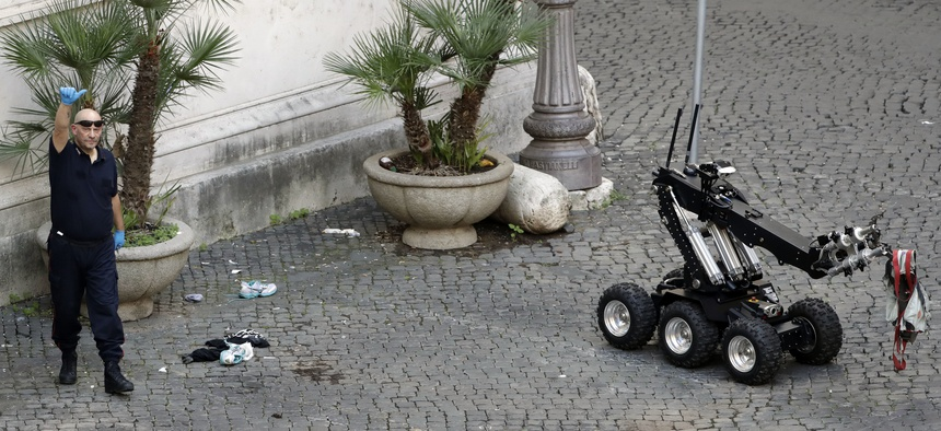 An Italian Carabinieri explosive expert gives the thumbs up sign near a bomb disposal robot after it detonated an unattended bag near Grazioli palace, former Italian Premier Silvio Berlusconi residency, in Rome, Oct. 8, 2016.
