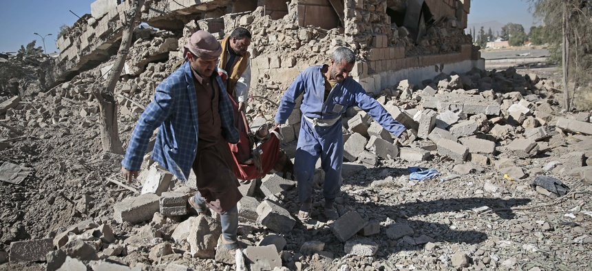 People carry the body of a man they uncovered from under the rubble of a Houthi-held detention center destroyed by Saudi-led airstrikes in Sanaa, Yemen, Wednesday, Dec. 13, 2017