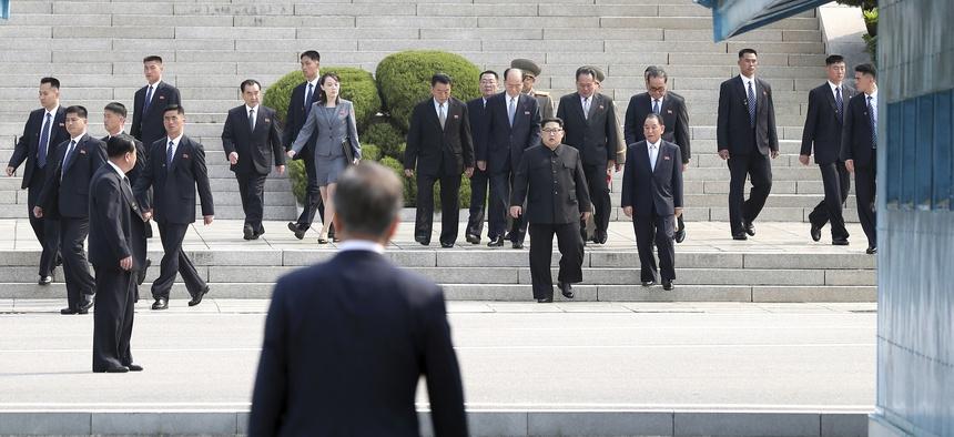North Korean leader Kim Jong Un, center, walks toward South Korean President Moon Jae-in at the border village of Panmunjom in the Demilitarized Zone, South Korea, Friday, April 27, 2018.