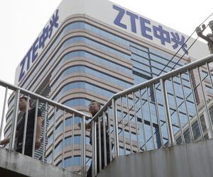 n this May 8, 2018, photo, Chinese men pass by a ZTE building in Beijing, China. President Donald Trump's weekend social media musings about China injected new uncertainty into the Washington's punishment of Chinese tech giant ZTE.