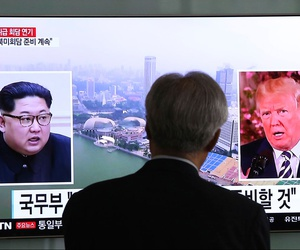 A man watches a TV screen showing file footage of U.S. President Donald Trump, right, and North Korean leader Kim Jong Un during a news program at the Seoul Railway Station in Seoul on May 16.