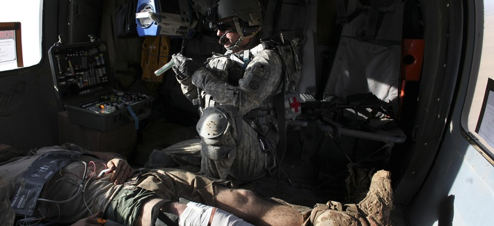 Airborne in a Black Hawk helicopter, U.S. Army flight medic Staff Sgt. Robert B. Cowdrey, of La Junta, Colo., with Charlie Company, All American Dustoff, attends to a U.S. Marine wounded in a rocket-propelled grenade attack, over Marjah, Helmand province,