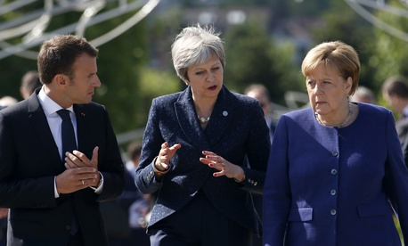 German Chancellor Angela Merkel, right, speaks with French President Emmanuel Macron, left, and British Prime Minister Theresa May after meeting at a hotel on the sidelines of the EU-Western Balkans summit in Sofia, Bulgaria, on May 17, 2018.