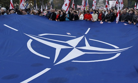 Demonstrators carry a huge banner with a NATO sign and Georgian national flags during a rally in Tbilisi, Georgia, on Nov. 15, 2014
