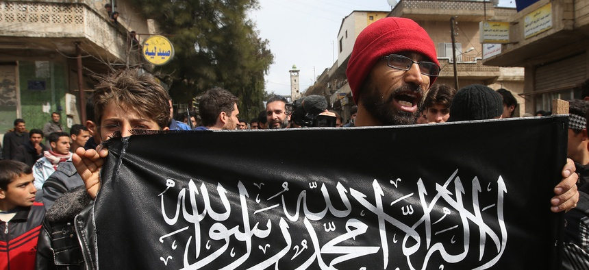 A 2013 photo of a man holding a Jabhat al-Nusra flag in Syria's Idlib province. The group has since rebranded itself Hayat Tahrir al-Sham, or HTS.