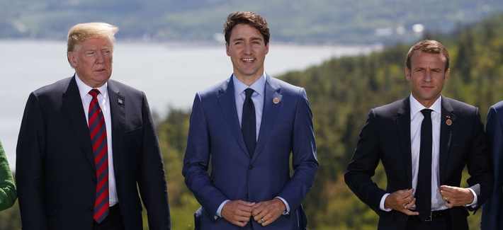 President Donald Trump, Canadian Prime Minister Justin Trudeau, and French President Emmanuel Macron participate in the family photo during the G-7 Summit, Friday, June 8, 2018, in Charlevoix, Canada.